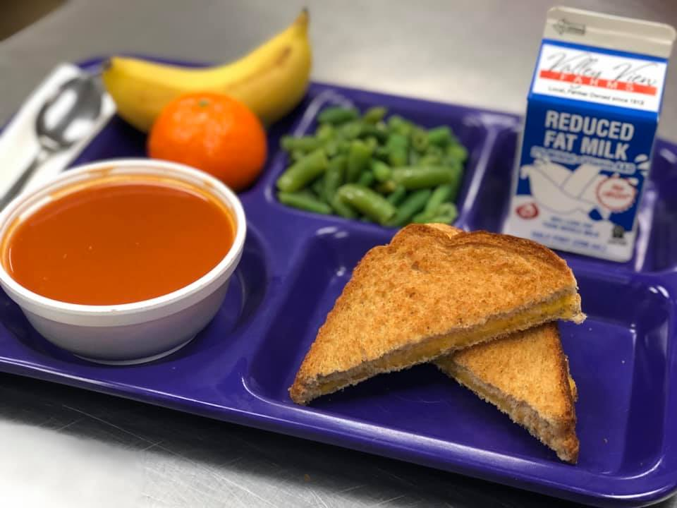 Café #110 lunch tray with tomato soup, whole wheat toast, green beans, fruit and milk